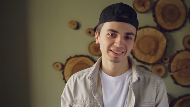 Zpomalené pohledný mladý muž v černé, bílé tričko a béžové tričko při pohledu na fotoaparát a směje se. Atraktivní lidé a módní koncept