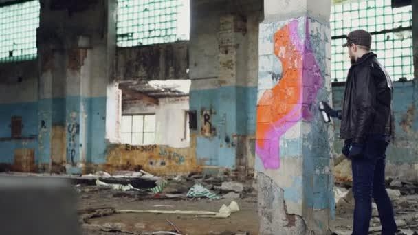 Mladý muž graffiti umělec je malování na pilíři ve staré budově špinavé aerosolových sprejů. Tvrdý chlap má na sobě modré džíny, bundy a ochranné rukavice