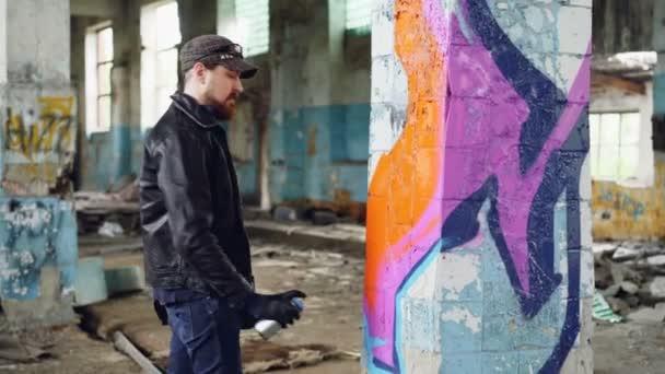 Szép szakállas fickó graffiti művész festészet a spray-festék elhagyatott épületébe. Modern street art, az ifjúsági szubkultúra és a kreatív emberek koncepció.