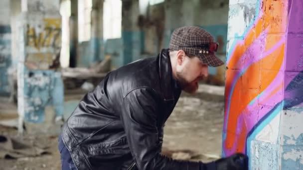 Handosme muž graffiti umělec je soustředěna na montážní linky s aerosolové barvy na sloupec ve starém prázdném domě. Opuštěné budovy, zdi umění a kreativní koncept