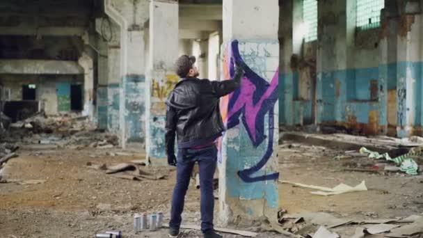 Malíře graffiti v neformálním oblečení je kresba s barva ve spreji na sloupec v prostorné opuštěné budovy. Abstraktní obrazy, moderní umění, kreativní lidi a bokovky koncepce