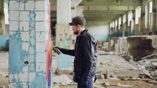 Boční pohled na graffiti umělec vousatý chlap na poškozené sloupce uvnitř emply průmyslová budova použití světlé aerosolové barvy. Koncept kreativity a lidi