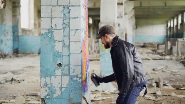 Hezký vousatý chlap drží aerosolové Malování a kreslení graffiti na pilíř uvnitř prostorné opuštěného domu. Kreativní lidé, prázdných budov a koncept moderního umění