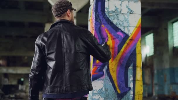 Rear View Of Male Graffiti Artist In Leather Jacket Painting On Damaged Column Inside Empty Industrial Building Young People Creativity Casual Clothing And Modern Art Concept