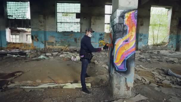 Férfi graffiti művész régi sérült oszlop, belül üres ipari épületben, absztrakt képek díszíti. Modern festő használ aeroszol spray festék