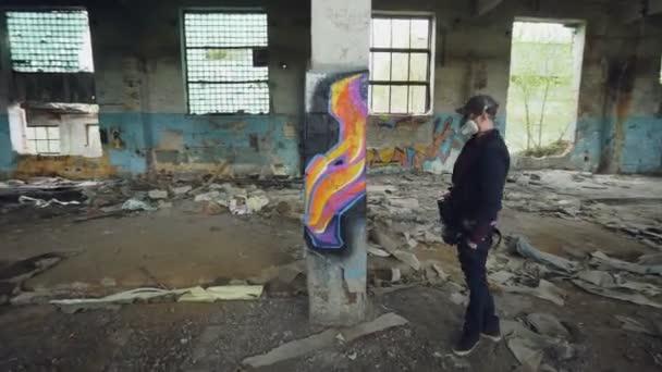 Graffiti festő védő maszk és kesztyű a rajz oszlopra régi piszkos üres épület, aeroszolos festék. A fiatalember visel, alkalmi ruhák és kap.
