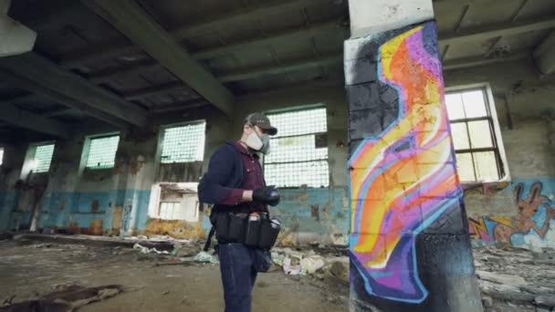 Városi utcai művész festészet graffiti elhagyott épület piszkos falak és ablakok, ő használ festék spray. Modern grafika és a kreatív emberek koncepció