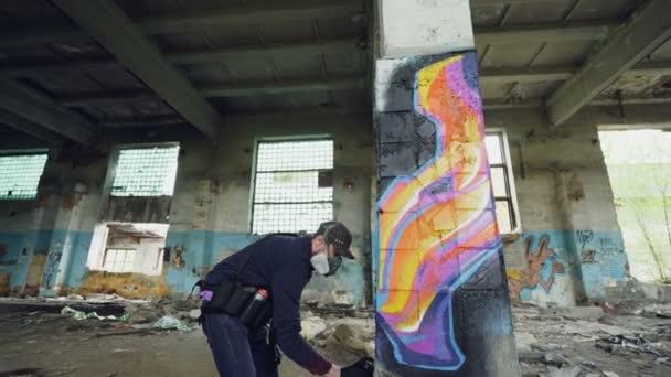 Nízký úhel výstřelu mladého muže je obličej maska Malování graffiti na sloupce uvnitř prázdné průmyslové budovy pomocí sprejů. Dirty poškozené zdi, okna a strop jsou viditelné