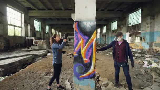 Mladí lidé graffiti umělci používají aerosolové barvy zdobí opuštěné průmyslové budovy s moderní graffiti obrázky. Tvořivost, pouliční umění a lidé koncepce