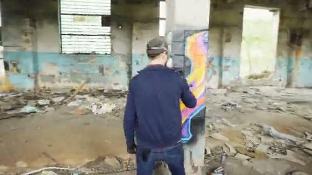 Gyorsított graffiti művészek aeroszolos festék segítségével díszíteni elhagyott ipari épületben modern graffiti képek. Kreativitás, a street art és a nép fogalma