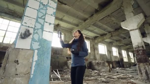 A vonzó lány városi művész festészet graffiti elhagyott épület piszkos falak és ablakok, ő használ festék spray. Modern grafika és a kreatív emberek koncepció