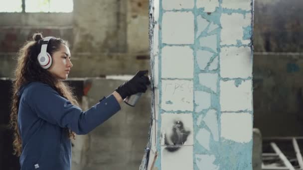 Pittore femminile graffiti è creazione immagine astratta su pilastro in vecchio magazzino danneggiato e ascolta la musica con le cuffie. Arte moderna e il concetto di persone creative