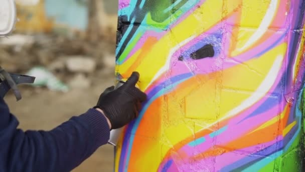 Zár-megjelöl szemcsésedik-ból hím kéz a bőr kesztyű holding spray festék, festészet graffiti a régi pillér elhagyatott épületébe. Modern művészetek, absztrakt képeket és emberek koncepció.