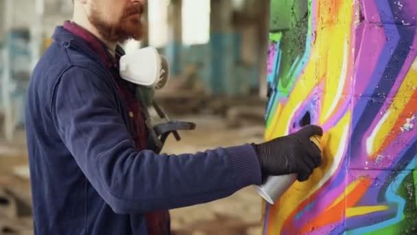 Vousatý muž graffiti malíř používá aerosolové barvy zdobí pilíř v staré průmyslové budovy. Moderní městské umění, kreativní mladí lidé a hobby koncepce