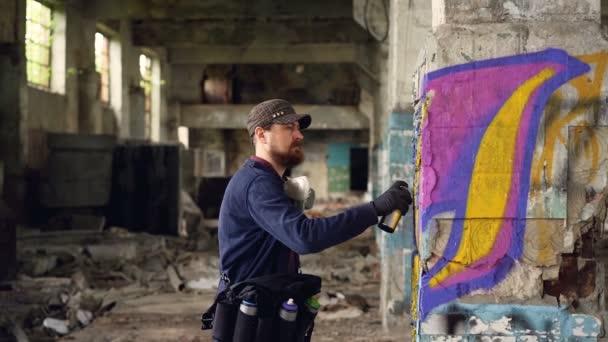 Mladý muž, profesionální graffiti malíř pracuje uvnitř opuštěné budovy, maluje s aerosolových sprejů na poškozené sloupce. Moderní koncepce umění a tvořivost
