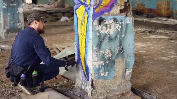 Moderní graffiti malíř je obsazení poblíž sloupec ve staré opuštěné budovy a malování graffiti s barva ve spreji vytváří jasný obraz. Kreativní koncept lidí a umění