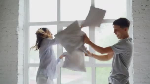 Excited young people are having pillow fight on double bed, they are having fun jumping and laughing. Happy couple, romantic relationship and entertainment concept.