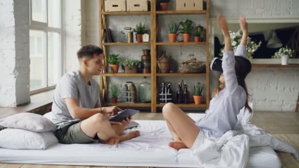 junge Frau benutzt Virtual-Reality-Brille, bewegt Hände und Körper, während ihr Freund den Laptop-Bildschirm berührt, seine Freundin ansieht und lacht.