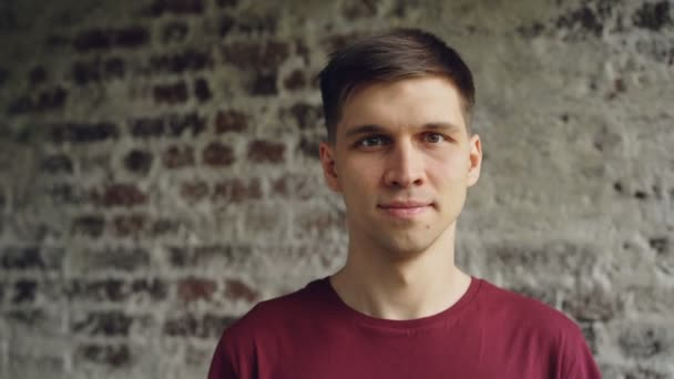 Detail portrét tmavovlasý pohledný mladý muž v světlé tričko s úsměvem a při pohledu na fotoaparát. Mladí lidé, loft stylu interiéru a štěstí koncept
