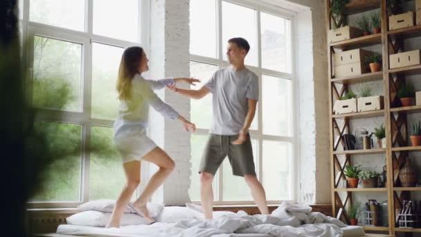 Zpomalený pohyb roztomilý pár tančí na posteli, skákání a směje se společně baví na víkendové ráno v lehké a pohoda. Šťastní lidé a zábava koncept