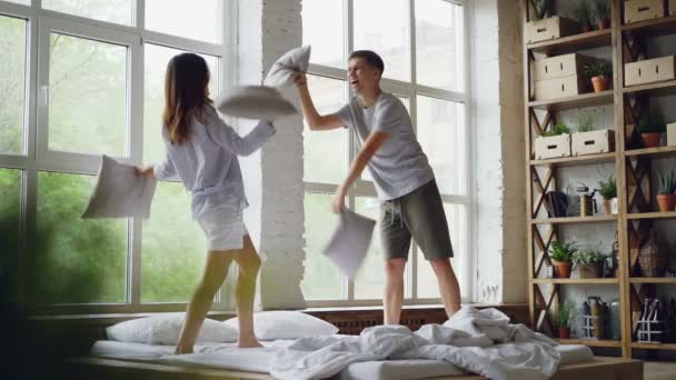 Slow motion of excited young people having pillow fight on double bed, they are having fun jumping and laughing. Happy couple, relationship and entertainment concept.