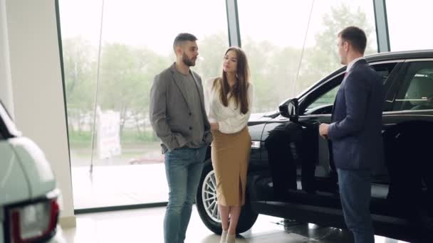 Attractive couple is talking to car sales manager in luxury car dealership and looking at beautiful black automobile. Luxurious autos and people concept.