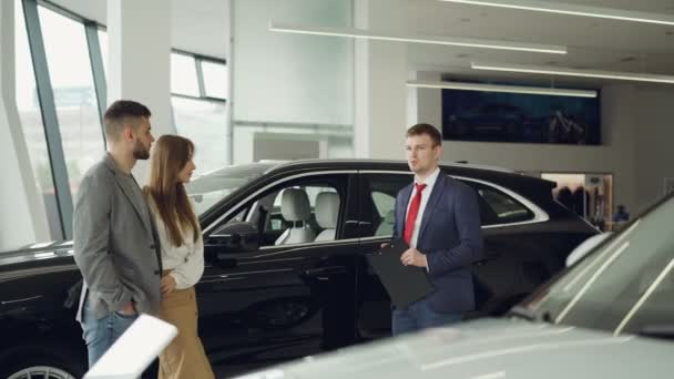 Car dealership worker is talking to beautiful couple bearded man and his attractive wife while standing near luxury car in auto salon. Choosing new automobile concept.