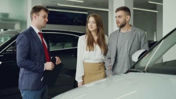S dětmi auto prodejce mluví s sebevědomý mladý muž mu řekl o novém modelu vozidla, když krásná žena stojí u její manžel drží ruku a usmívá se.