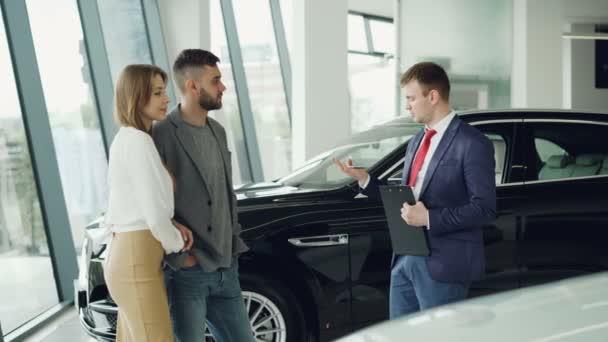 O: pár muž a žena se mluví vedoucímu do autodům, zatímco jim vypráví o luxusní auto modelu. Krásní lidé, dopravní a obchodní koncepce.