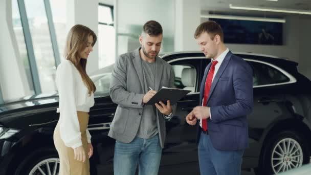 Hezký mladý muž je podepsání kupní smlouvy v autodům, získali klíčenky od prodejce a dává své manželce, ona se usmívá a políbila ho