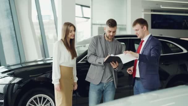 Mladí, vousatý muž nekupuje auto pro manželku atraktivní podepisování dokumentů, třesoucí se ruce s manažerem a získání klíčenky pak dávat ženě, ona je objímala a líbala ho.