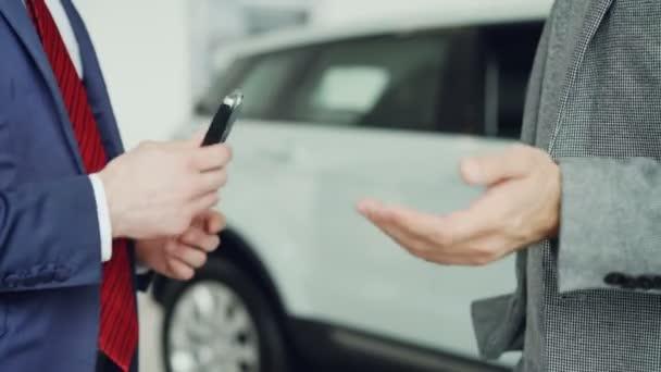 Zblízka střílel z mužských rukou dostat klíče od auta po úspěšné dohodě s vedoucí prodeje a potřesení rukou. Nákup a prodej auta, podnikatelé a handshake koncepce