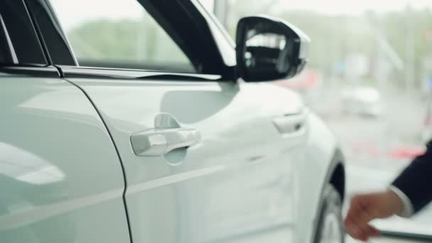 Close-up shot of male hand opening car door in auto dealership with large window in background. Selling automobiles, luxurious autos and salesperson concept.