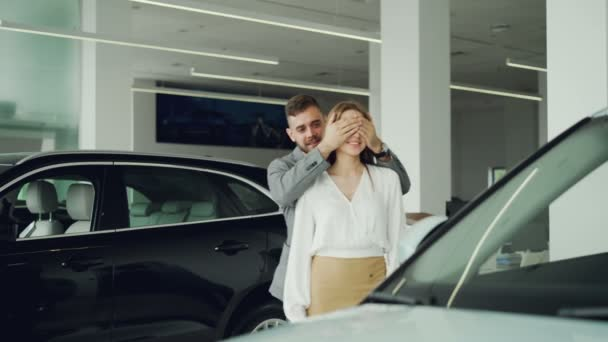 Atraktivní mladá žena je stále nové auto od svého přítele, on se zavírá oči a vede ji na auto v motoru obchodní zastoupení, jsou objímání a líbání.