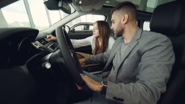 Pěkný chlap a jeho hezká přítelkyně jsou kontrola interiéru luxusní automobil v autodům. Muž sedí v sedadle řidiče drží kolo, dívka se dotýká autodíly