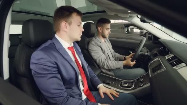 Boční pohled na dva muži zákazníka a prodavač seděl v krásném autě na předních sedadlech a mluvící dojemné automobilových dílů. Vousatý kupující kontroluje kvalitu auto a funkce
