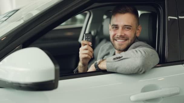 Detailní portrét vousáč nový majitel auta sedí uvnitř krásné automobilové hospodářství klíčenky a usmívá se, při pohledu na fotoaparát. Koncept dopravy a lidé.
