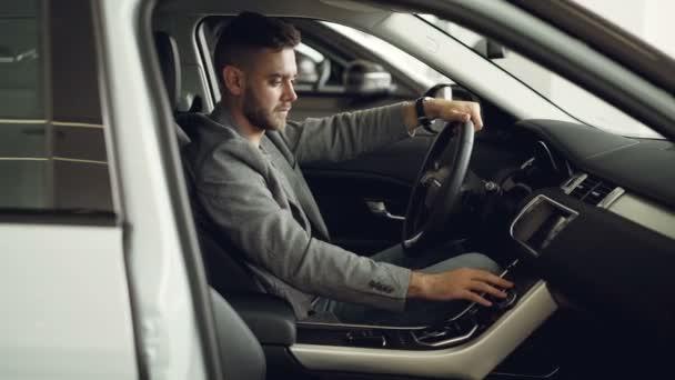 Vážný mladý muž sedí uvnitř nové auto v motoru showroomu a kontrola elektroniky stisknutím tlačítka na ovládacím panelu dotýkání dílů. Nákup automobilů koncept