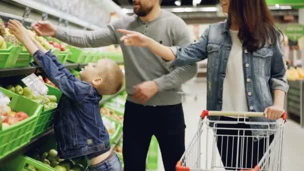 Šťastné mladé rodiny matka, otec a dítě se nákup ovoce v supermarketu ananas v nákupní košík, mluví a usmíval se. Potraviny obchod a lidé koncept