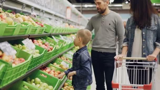 Mladá Rodina Máma, táta a malého chlapce výběr ovoce v supermarketu dojemné a vonící je a uvedení do vozíku. Nakupování potravin a lidé koncept.
