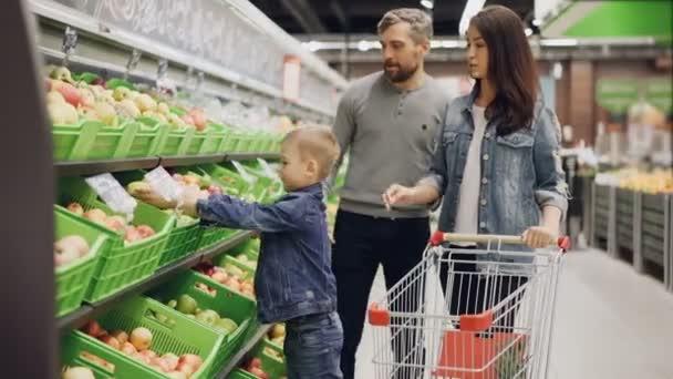Mladá rodina s dítětem je nakupování potravin v supermarketu, rodiče vybírají ovoce a chlapec je vložíte do nákupního košíku. Obchod s potravinami a rodinný život koncept.