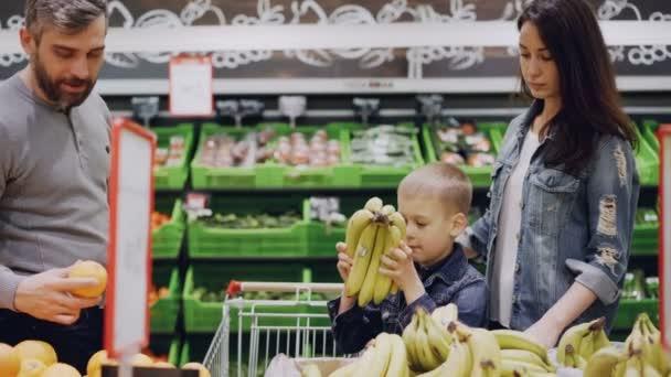 Maminka, Tatínek a roztomilý chlapec volí uložení ovoce v potravinách, dítě je vonící banány a dávat je do svého otce, člověk je uvedení ovoce do nákupního vozíku