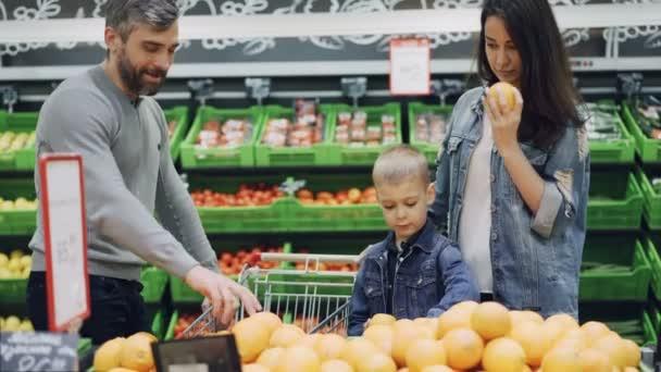 Felice famiglia è la scelta di arance in supermercato, padre madre e ragazzo sveglio sta assumendo frutta, sentente lodore li poi mettere nel carrello. Concetto di cibo e gente acquisto.