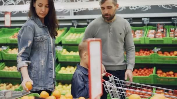 Young family with cheerful child is walking through food store with shopping cart and choosing fruit smelling and touching them. Buying food and people concept.