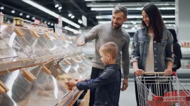 Roztomilý chlapeček je pomoci rodičům vybrat chléb v pekárně oddělení v obchod s potravinami, on bere bochník a to pak dát do košíku