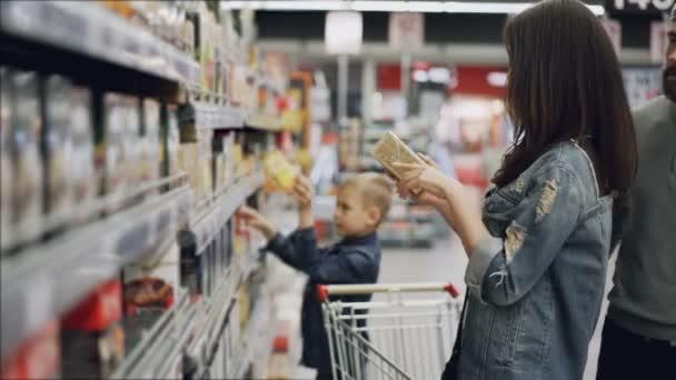 Mladá žena je volba čaje v obchod s potravinami, její manžel a syn pomáhají jí při pohledu na produkty a mluví. Nákup potravin a nápojů v supermarketu koncepce