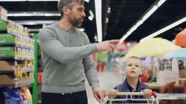 Cheerful man is shopping with his joyful child, they are walking with shopping trolley in supermarket looking around, pointing at goods, talking and laughing.