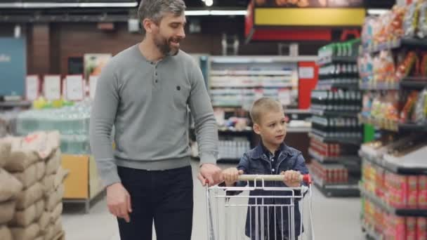 Dolly shot of young family father and son walking through food store with trolley looking around and talking. Shopping together, happy people and supermarket concept.