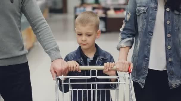 Rozkošné dítě tlačí nákupní vozík uvnitř obchod s potravinami, mu pomáhají jeho milující rodiče. Děti, mladá rodina, supermarketu a každodenní rutinní koncepce