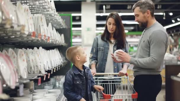 Young family is choosing bowls in supermarket in kitchenware department, they are holding goods comparing them and talking, little boy is helping his parents.